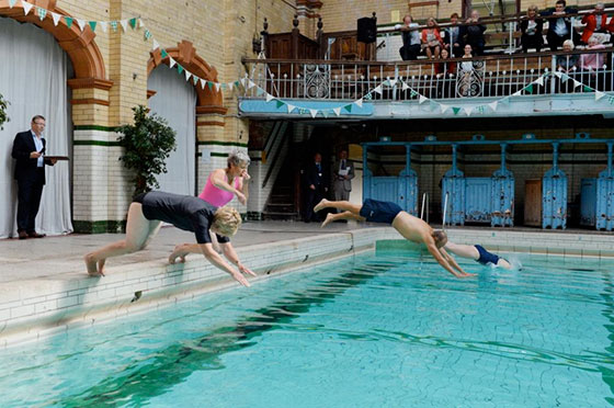 People diving into a swimming pool